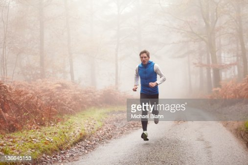 Man running along countryside road in fog : Stock Photo