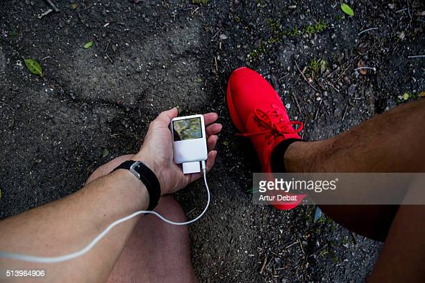 Man running and checking from personal point of view his mp3 player with earphones and wearing a red trainers in the road asphalt.