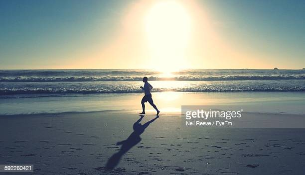 Man Running At Beach Against Sky During Sunset