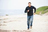 Man running at beach smiling moving towards camera