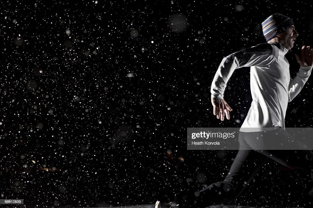 Man running at night in snowstorm. : Stock Photo