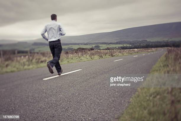 Man running down an empty country road.