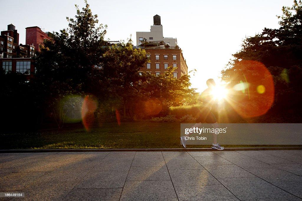 Man running in city at sunset