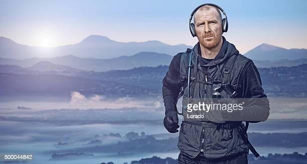 Mann läuft in Bergen bei Sonnenaufgang
