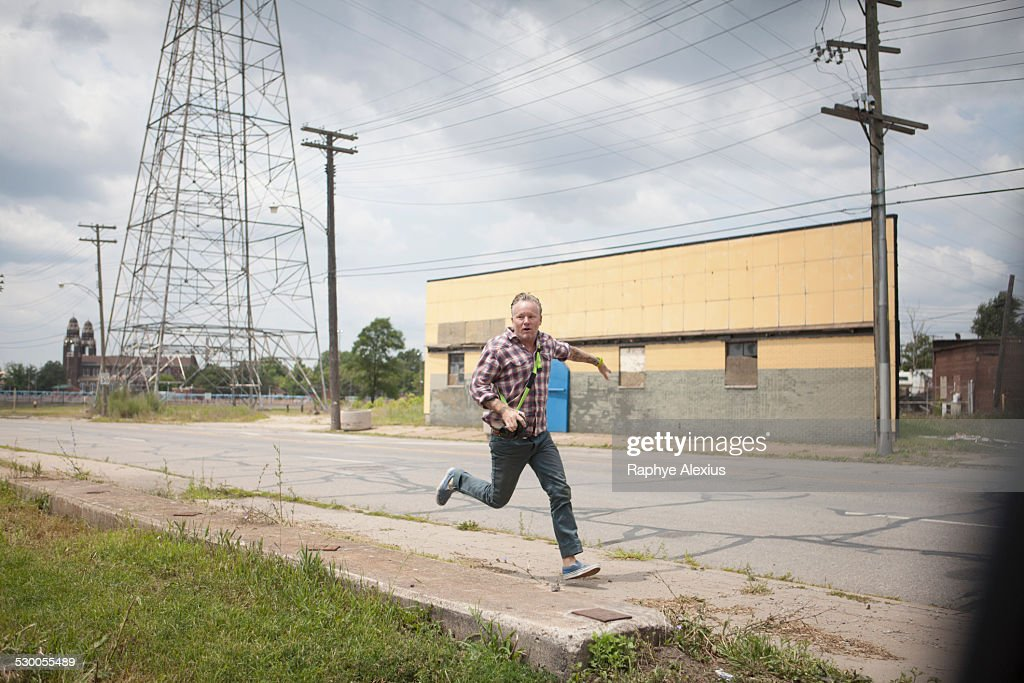 Man running in panic along industrial road, Detroit, Michigan, USA