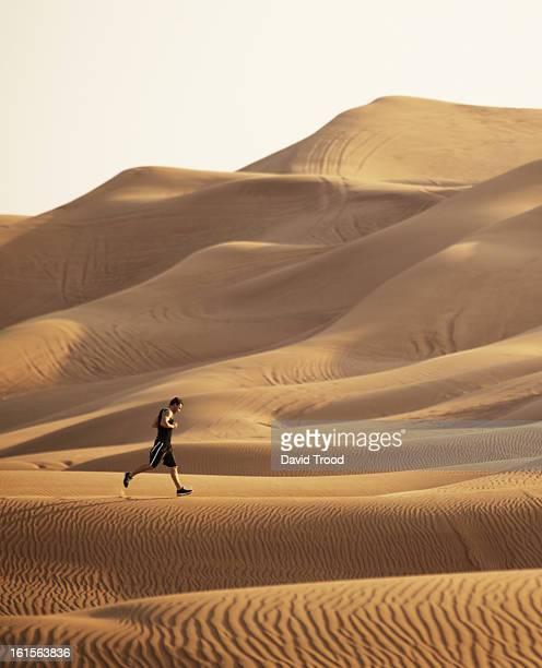 Man running in sand dunes