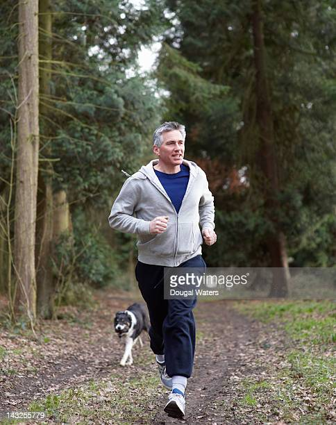 Man running in woodland with dog.
