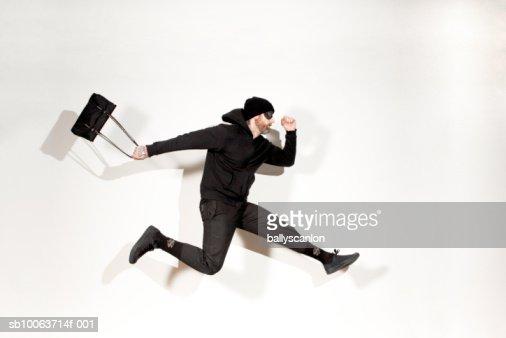 Man running mid-air with handbag, side view : Stock Photo