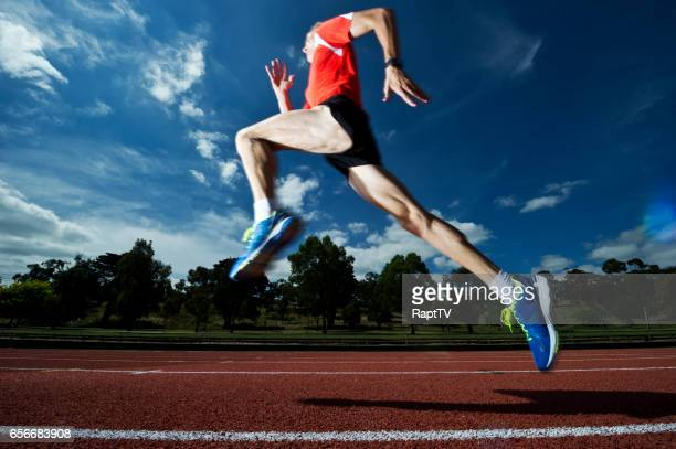 A man running on an athletics track takes a big stride.