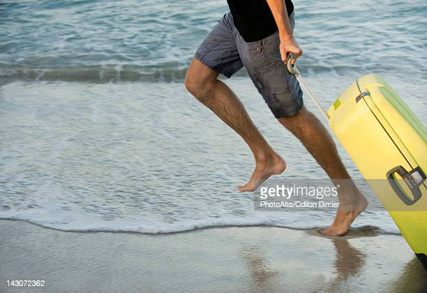 Man running on beach with suitcase