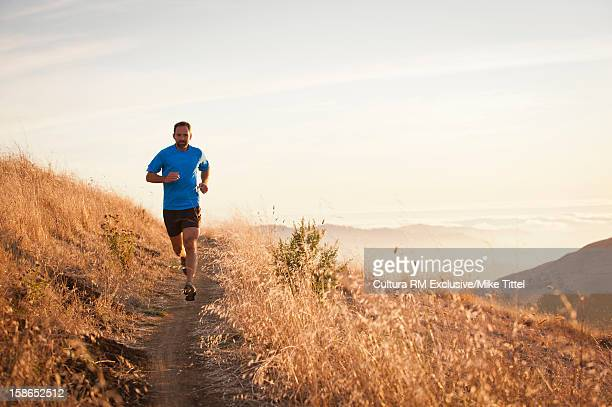 Man running on grassy hillside