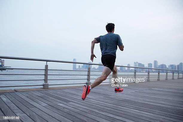 Man running on pier in front of city skyline