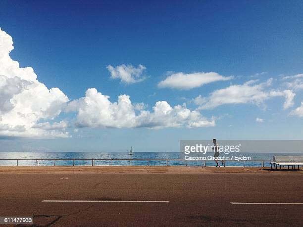 Man Running On Sidewalk By Sea Against Sky