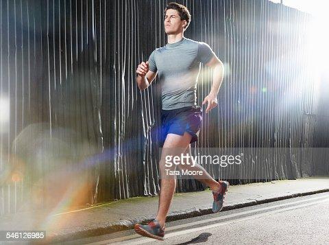 Man running on sunny street in urban setting