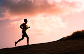 Fitness male running outdoors during sunset. Healthy lifestyle concept.