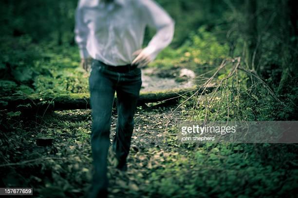Man running through forest