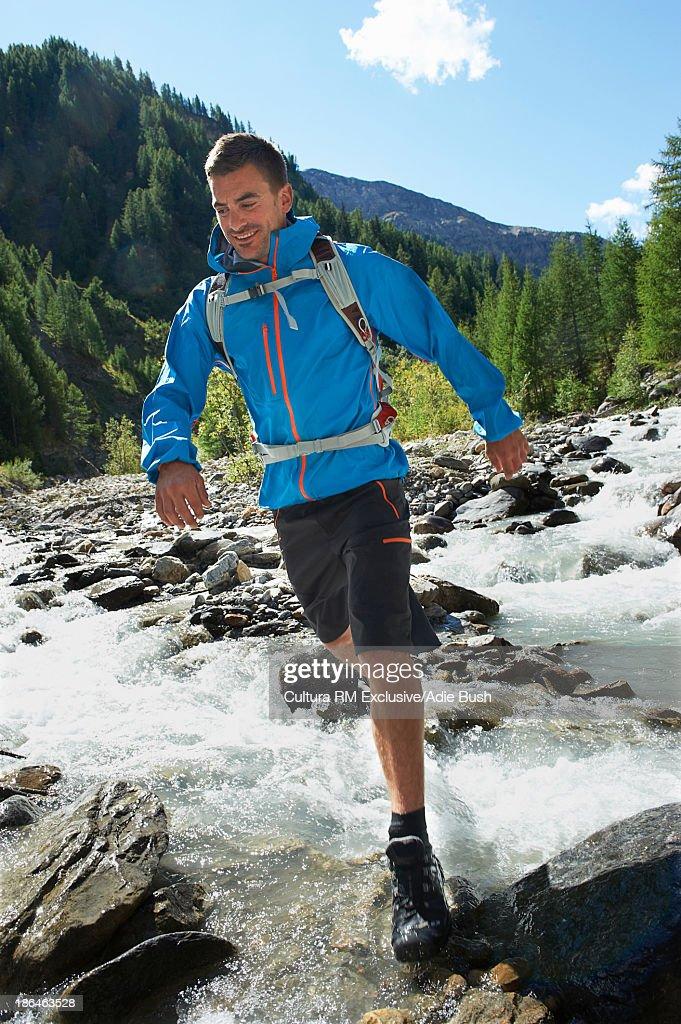 Man running through river, Chamonix, Haute Savoie, France : Stock Photo
