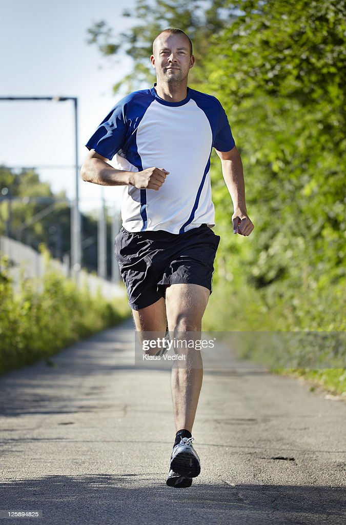 Man running towards camera smiling : Stock Photo
