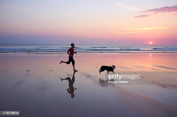 Man running with dog at beach.