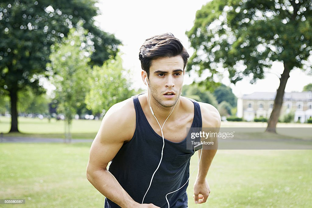 man running with headphones in park : Stock Photo