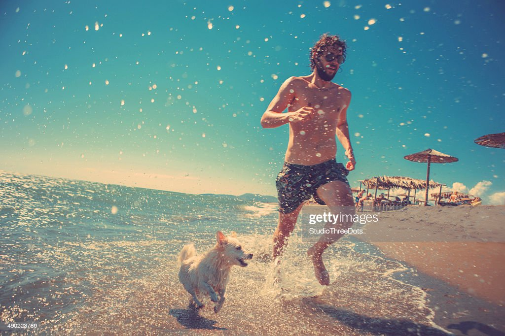 man running with his dog on the beach : Stock Photo