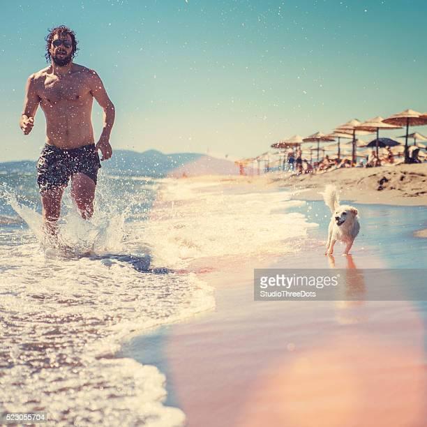 Un homme qui court avec son chien sur la plage