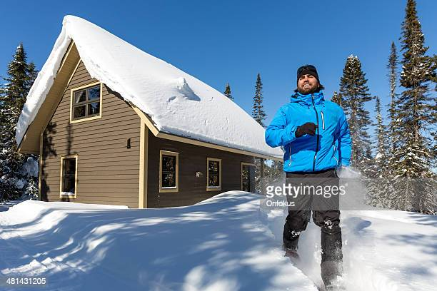 Man Running with Snowshoes and Wooden Chalet in Powder Snow