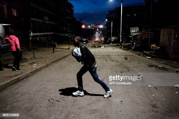 A man runs across a street carrying his child while protesters gather around a burning barricade in the Mathare slums in Nairobi on October 30 during...