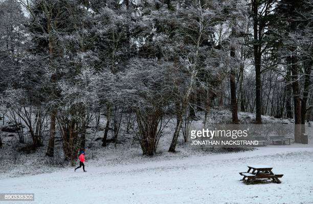 A man runs after snow fall on December 11 2017 in Sundbyberg near Stockholm High winds and heavy snow in Europe on Monday stranded thousands of...