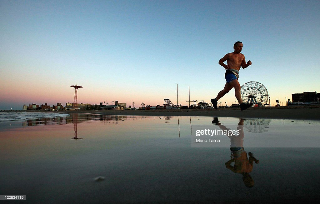 A man runs along the beach at Coney Island at dawn on August 29, 2011 in the Brooklyn borough of New York City. Hurricane Irene wreaked havoc on the East Coast and slowly weakened into a tropical storm before making a third landfall at Coney Island. Irene left at least 24 dead across eight states.