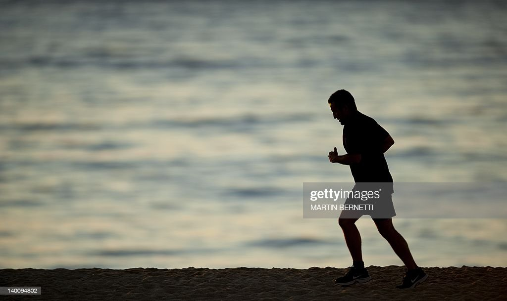 A man runs along the beach during sunset on the Bay of Valparaiso, in Viña del Mar, Chile, on February 27, 2012. AFP PHOTO/MARTIN BERNETTI