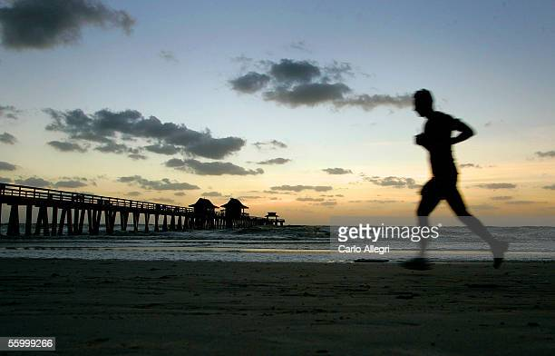 A man runs along the beach near Naples Pier as the sun sets after Hurricance Wilma hit earlier in the morning October 24 2005 in Naples Florida Wilma...