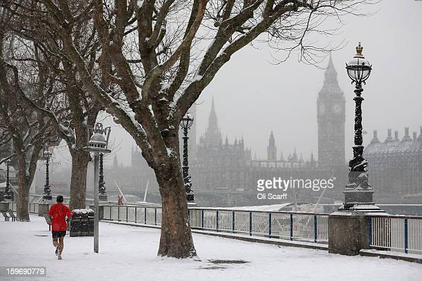 A man runs along the South Bank of the river Thames as snow falls on January 18 2013 in London England Widespread snowfall is affecting most of the...