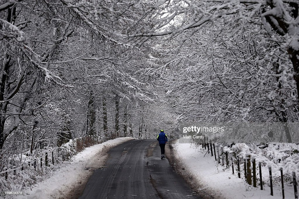 A man runs among the snow covered trees surrounding the grounds close to the National Trust's Stourhead on January 21, 2013 in Wiltshire, England. As the UK's cold snap continues, parts of the country including the South West and Wales were bracing themselves for even more snow, forecast to arrive tonight and tomorrow.