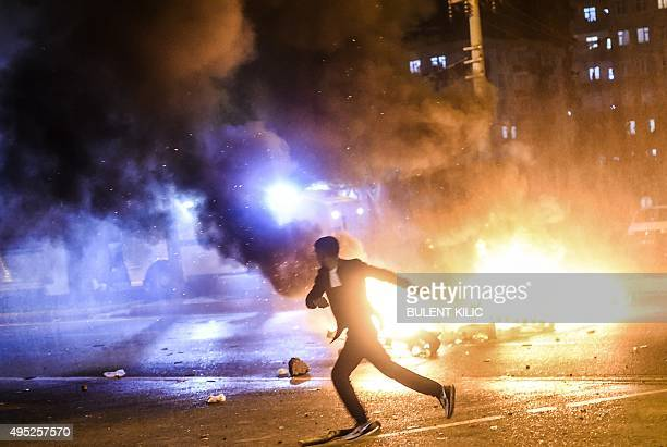 A man runs as smoke billows from burning pallets set on fire during clashes between Turkish riot policemen and Kurdish protesters in the southeastern...