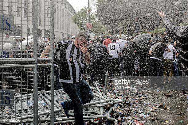 A man runs as Turkish antiriot police use tear gas and water cannon to disperse supporters around the stadium before the Turkish Spor Toto Super...