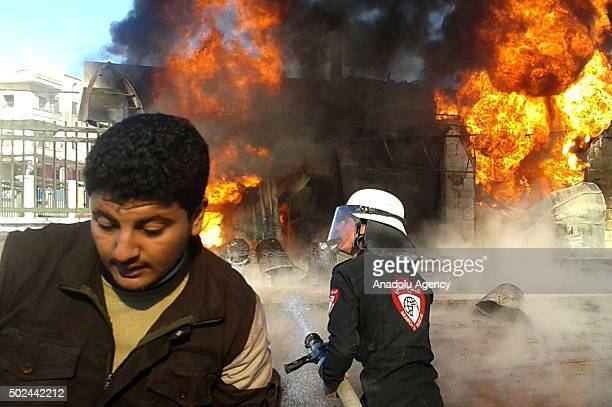 A man runs away as flames rise after the war crafts belonging to the Russian army carried out airstrikes on two hospital in the Azaz town of Aleppo...