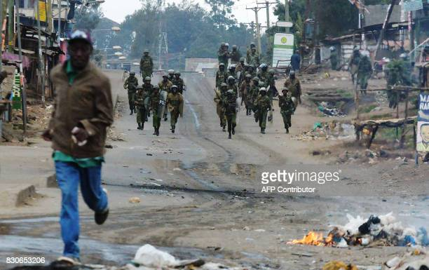 A man runs away from security forces patrolling during an operation to stem protest in Kawangware slum in Nairobi on August 12 2017 following...