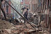 A man runs down a street covered in debris after buildings collapsed on April 26 2015 in Bhaktapur Nepal A major 78 earthquake hit Kathmandu midday...