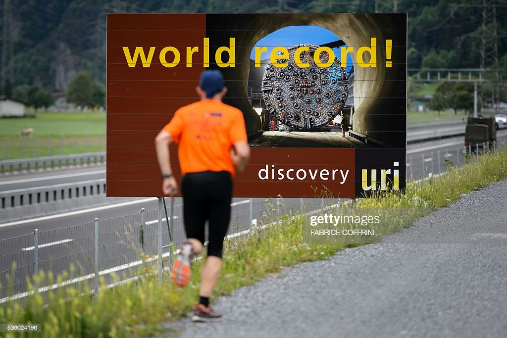 A man runs during his jogging past a board celebrating the world's longest train tunnel on the eve of its opening ceremony on May 31, 2016 in Attinghausen near Erstfeld. The new Gotthard Base Tunnel (GBT) is set to become the world's longest railway tunnel when it opens on June 1. The 57-kilometre (35.4-mile) tunnel, which runs under the Alps, was first conceived in sketch-form in 1947 but its construction only began 17 years ago. / AFP / FABRICE