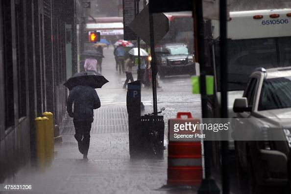 A man runs for cover during a heavy rain storm in Manhattan on June 1 2015 in New York City The tristate area has been expericening heavy rain with...