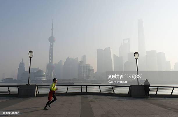 A man runs in smog at the Bund on December 29 2014 in Shanghai China Shanghai's realtime Air pollution index read high 203 on Monday morning