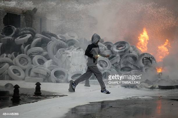 A man runs near a stack of burning tires as farmers protest in front of the prefecture early on August 19 2015 in SaintLo northwestern France AFP...