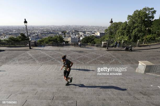A man runs on the deserted steps near the SacreCoeur Basilica in the neighborhood of Montmartre in Paris on August 9 2016 Many places and events in...