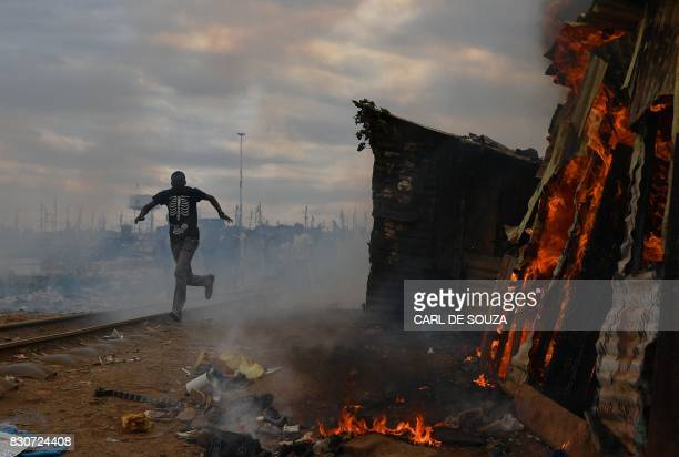 TOPSHOT A man runs past a shack which was burnt to the ground by protestors in the Kibera slum in Nairobi on August 12 2017 Three people including a...