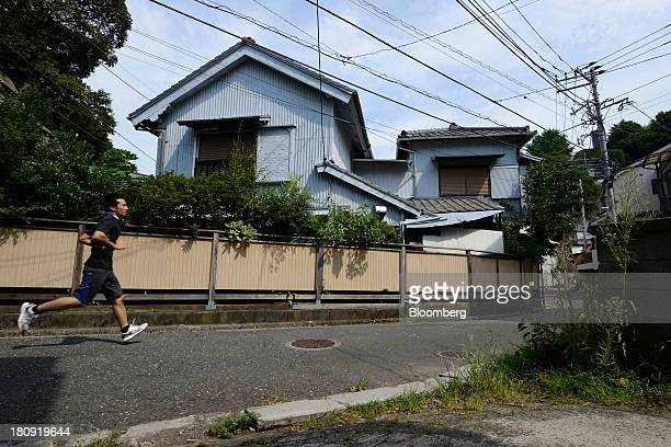 A man runs past a vacant house in the Yato area of Yokosuka City Kanagawa Prefecture Japan on Wednesday Aug 21 2013 More than 50 houses and...