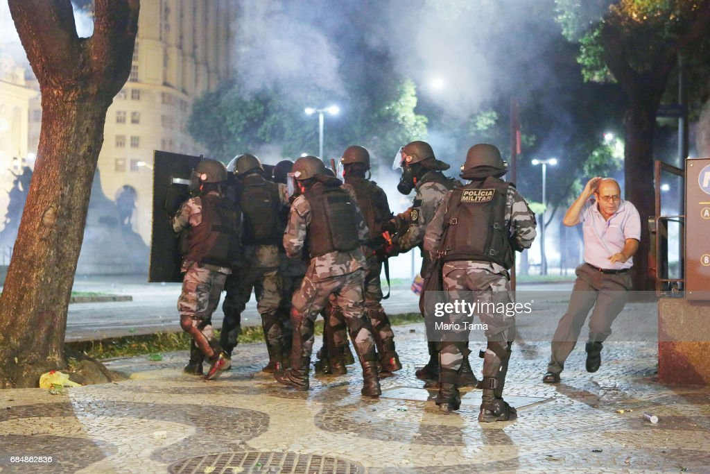 A man runs past Brazilian Military Police (PM) officers amidst tear gas during an anti-Temer protest on May 18, 2017 in Rio de Janeiro, Brazil. Thousands of protestors hit the streets of Rio in the aftermath of a recording allegedly revealing President Michel Temer endorsing bribery payments.