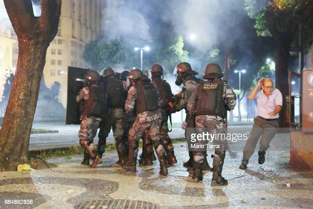 A man runs past Brazilian Military Police officers amidst tear gas during an antiTemer protest on May 18 2017 in Rio de Janeiro Brazil Thousands of...