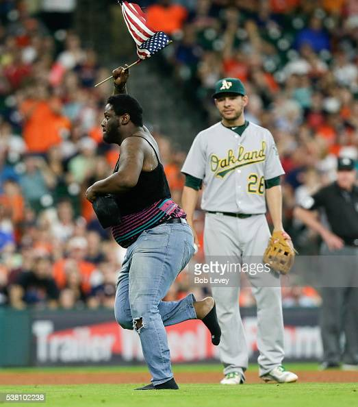 A man runs past Danny Valencia of the Oakland Athleticsonto the field in the fourth inning during a baseball game between the Oakland Athletics and...