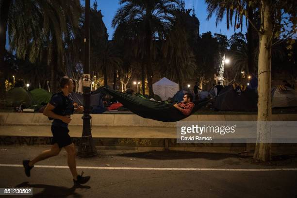 A man runs past demonstrators who spent the night in front of the Catalan High Court building on September 22 2017 in Barcelona Spain ProIndependence...